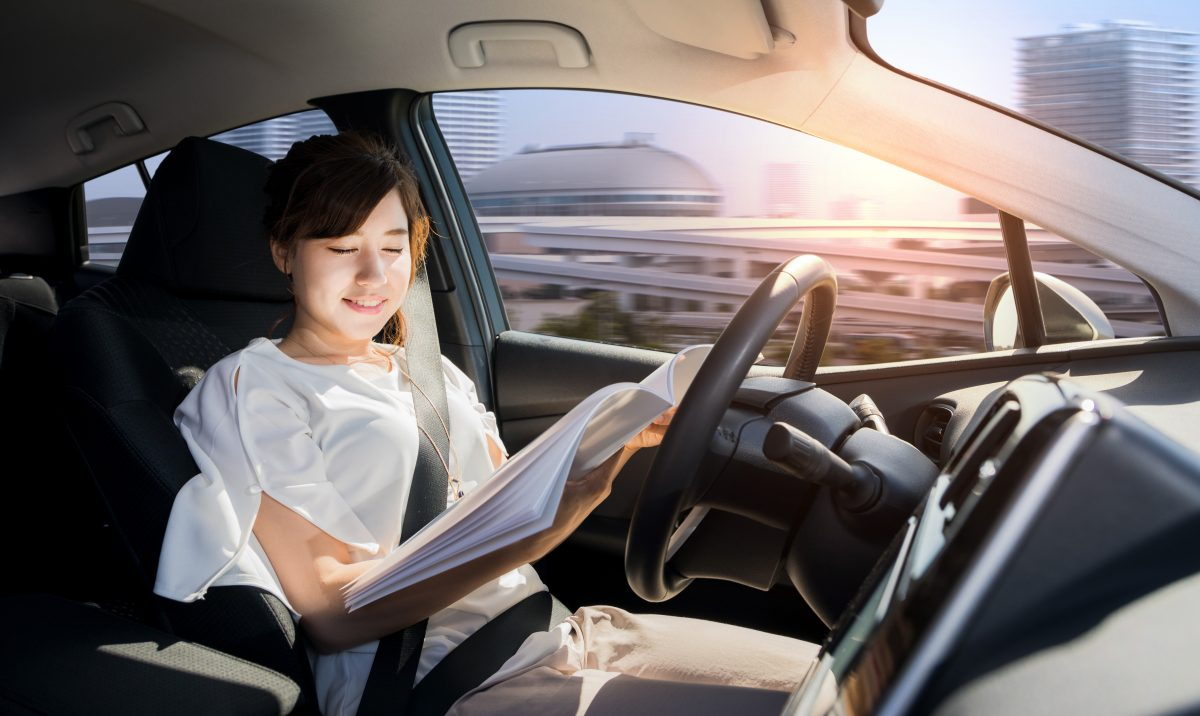 Young Woman Reading A Magazine In Autonomous Car. Self Driving Vehicle. Autopilot. Automotive Technology.